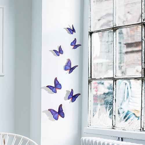 Sticker autocollant sur un mur blanc à côté d'une fenêtre représentant des papillons bleu indigo