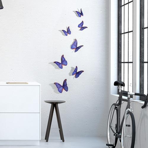 Sticker papillons bleu indigo déco sur un mur blanc de salon avec un vélo et une table basse