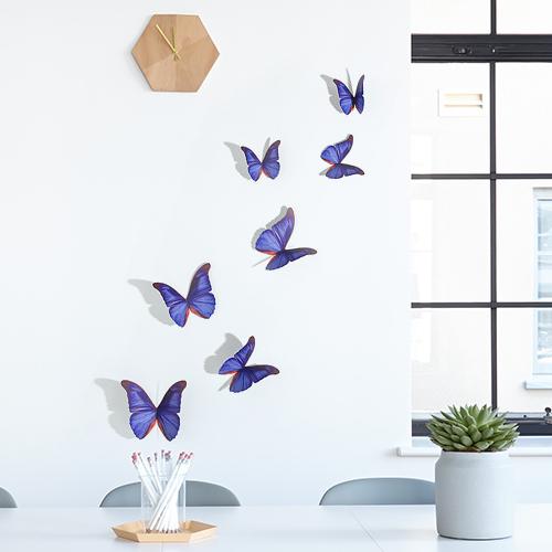 Sticker mural Papillons bleu indigo en dessous d'une horloge en bois sur un mur blanc