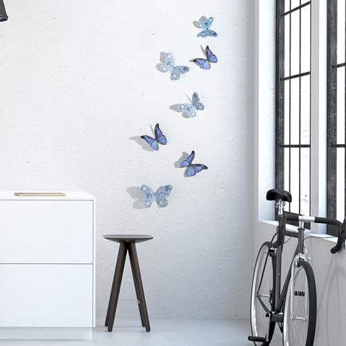 Stickers papillons mix bleu et liberty en 3D sur mur de salon avec un vélo et une fenêtre
