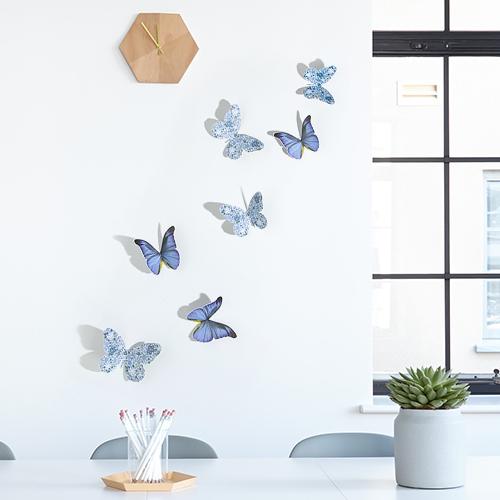 Stickers mix Papillons mix bleu et liberty sur un mur blanc avec une fenêtre et une horloge