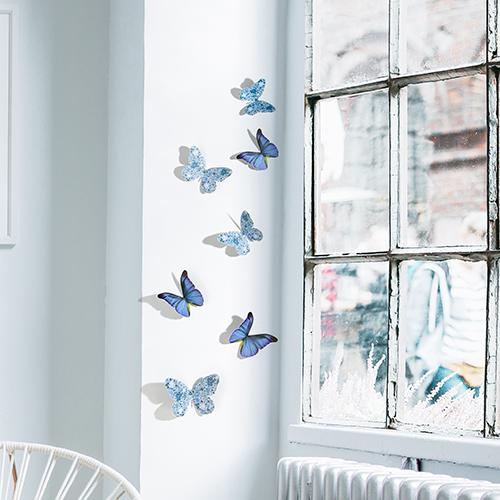 Sticker mural adhésif 3D papillons bleu collés sur un mur blanc
