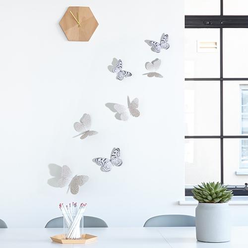 Sticker adhésif Papillons mixte noirs et blancs et manuscrit sur un mur blanc avec une horloge
