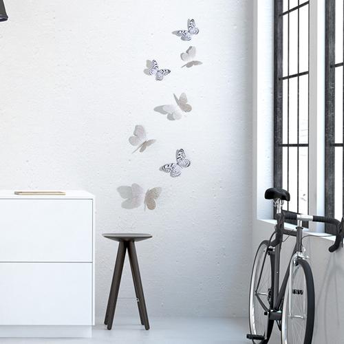 Sticker autocollant Papillons mixte noirs et blancs et manuscrit sur un mur blanc avec un vélo