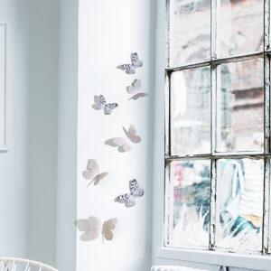 Sticker déco Papillons mixte noirs et blancs et manuscrit sur un mur blanc à côté d'une fenêtre
