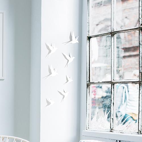 Sticker adhésif représentant des hirondelles blanches sur un mur avec un vélo et une petite table en bois