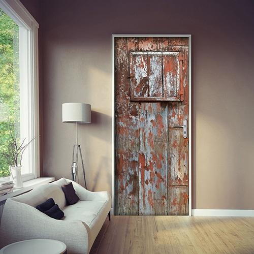 Vielle porte en adhésif collable dans un salon moderne avec des murs de couleur taupe. La peinture est écaillée avec un style vintage de vielle grange.