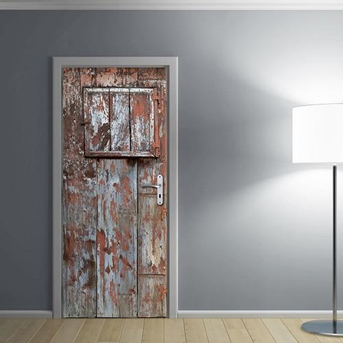 Porte adhésive sticker trompe l'oeil d'une porte de grange en bois délavé avec peinture écaillée