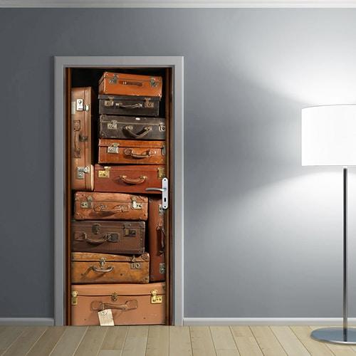 Valises Vintages collé sur une porte entourée d'un mur gris éclairé par une lampe pour colorer une pièce