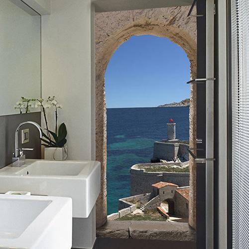 Sticker pour porte avec vue sur la mer turquoise et sur le bord de mer en présence d'un phare. Cet adhésif est installé dans une salle de bain moderne.