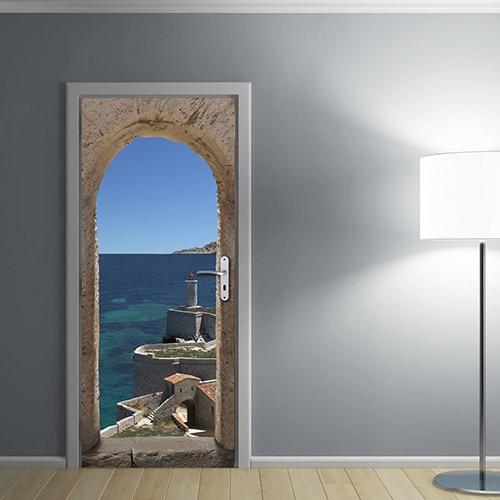 Sticker pour la porte d'une entrée faisant apparaitre la mer à travers la lucarne d'une vielle bâtisse. Sur l'adhésif on observe la mer turquoise et le phare de cette côte méditerranéenne.