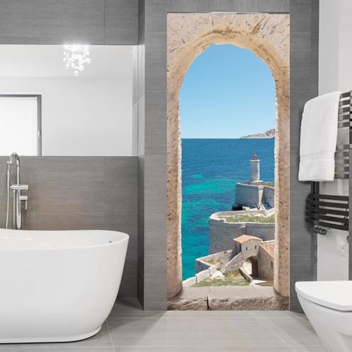Dans une salle de bain moderne grise et blanche on s'évade à l'aide de cet adhésif pour porte qui nous emmène au bord de la Méditerranée dans une vieux village entouré d'une forteresse