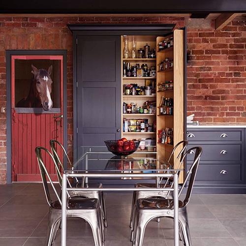 Sticker porte avec la tête d'un Cheval et Box rouge dans une salle à manger ou cuisine moderne. Les couleurs orange, rouge ocre, gris métal s'accordent parfaitement pour un résultat harmonieux.