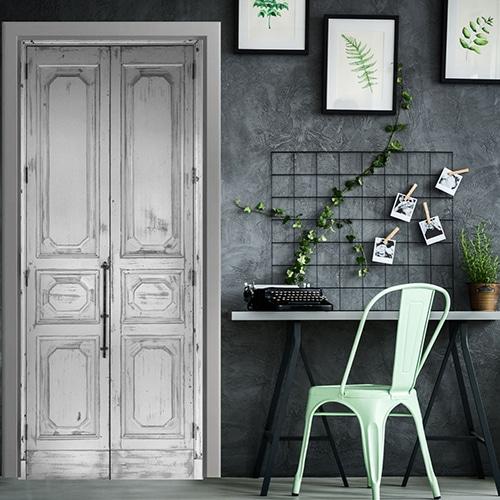 Sticker de porte composé d'un trompe l'oeil d'une vielle porte blanche patinée donnant un style design avec de l'ancien. Le décor est situé dans un bureau modern épuré