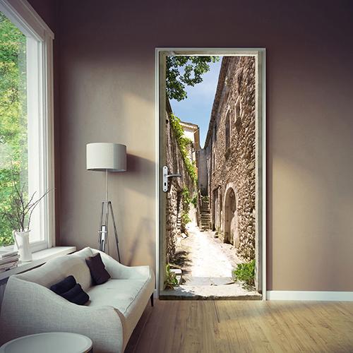Salon avec mur gris taupe et sticker adhésif autocllant dans un salon représentant une rue d'un village méditerranéen du sud de la france avec facades en vielles pierres et ciel bleu