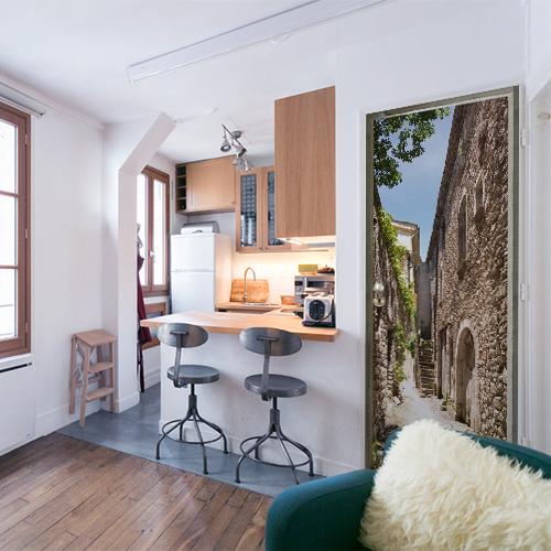 Appartement moderne dans lequel on trouve un sticker pour porte autocollant qui représente une vielle rue d'un village du sud de la france avec des vielles pierres et un ciel bleu
