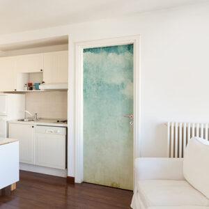 Cuisine moderne blanche dont la porte est décoré avec un sticker autocollant mer turquoise