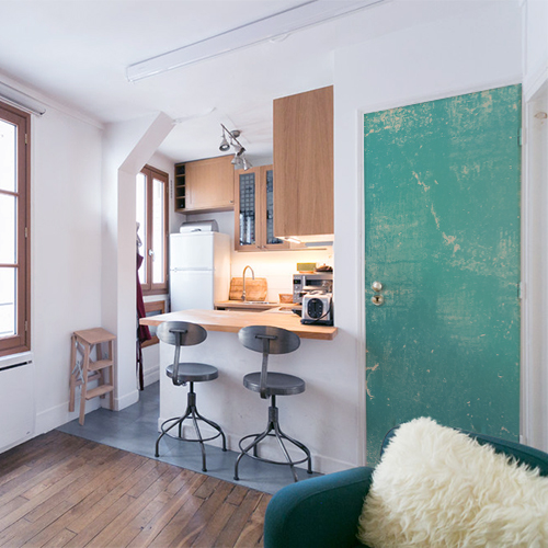 Petit studio avec un sticker autocollant turqoise abîmé collé sur la porte