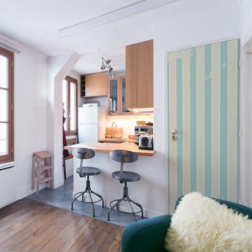Petit studio moderne bien agencé dont la porte d'entrée est décorée par un sticker déco rétro modèle cabine de plage