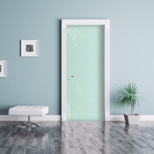 Sticker adhésif vert à pois blanc collé sur la porte d'entrée d'un studio moderne blanc avec plante et tabouret design mur bleu clair pastel