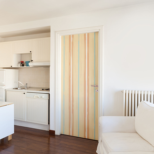 Appartement blanc dont la porte d'entrée près de la cuisine est décorée par un sticker déco cabine de plage