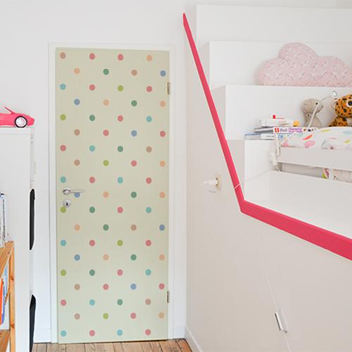 Chambre d'enfants dont la porte est décorée par un sticker autocollant multicolores à pois