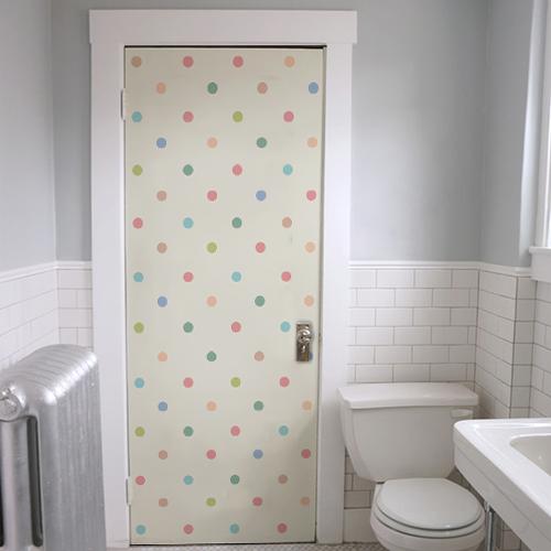 Salle de WC avec un sticker adhésif à pois multicolores sur la porte pour la salle de bain blanche