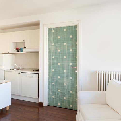Salle de séjour blanche avec un sticker vert à pois blancs sur la porte