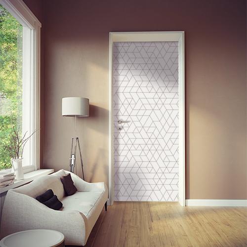 Salle de séjour moderne dont la porté est ornée d'un sticker autocollant motifs géométriques blancs et noirs