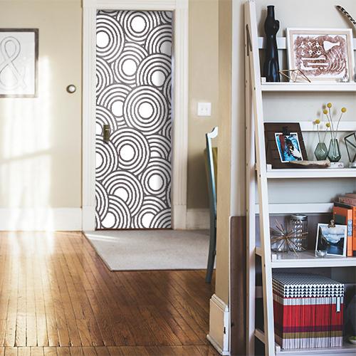 Porte d'entrée d'une maison familiale qui est décorée avec un sticker pour porte modèle ronds blancs et noirs