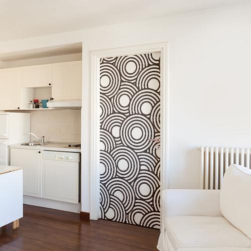 Studio dont la décoration blanche est mise en valeur par un sticker cercle blanc collé sur la porte