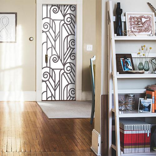 Maison décorée dont la porte est ornée d'un sticker blanc et noir imitation vitraux