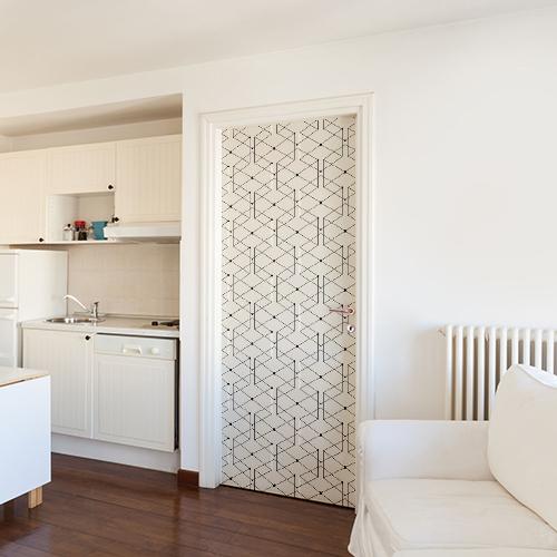 Pièce à vivre blanche dont la porte est ornée par un sticker géométrique blanc et noir
