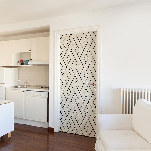 Sticker géométrique blanc et noir collé sur la porte de la maison qui est toute blanche