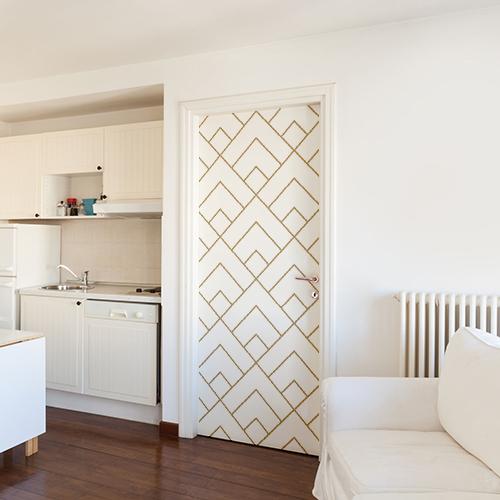 Petite pièce à vivre dont la porte d'entrée est décorée par avec un sticker autocollant mosaïque de pyramides blanches et or