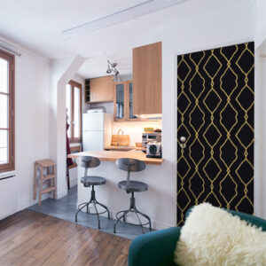 Petit studio bien agencé avec un sticker Renaissance noir et or collé sur la porte d'entrée