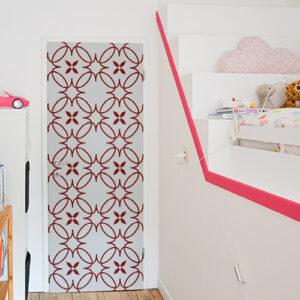 Chambre d'enfant dont la porte est décorée avec un sticker autocollant décoratif modèle rouge et blanc imitation céramique