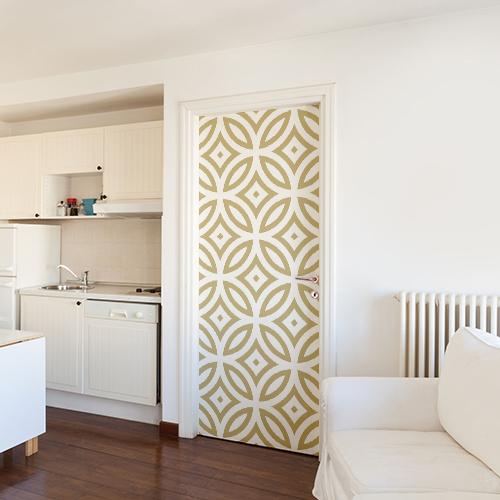 Grand studio aux murs blancs décoré avec un sticker frise géométrique dorée et blanche collée sur la porte.
