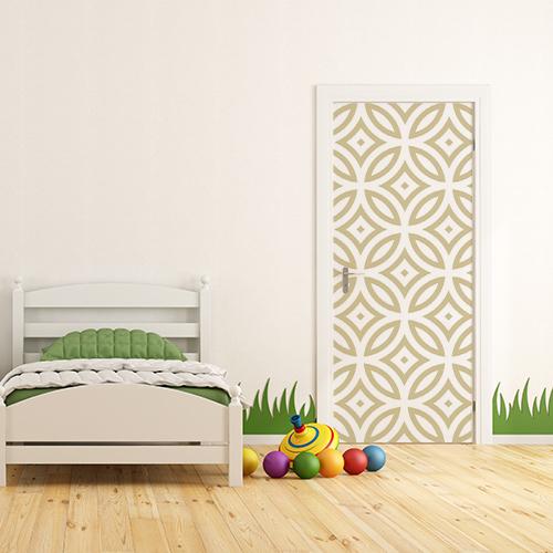 Chambre d'enfant avec un sticker autocollant blanc et or collé sur la porte d'entrée avec lit et jouets pour créer un univers et un monde imaginaire