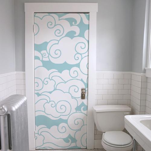 Salle de WC dont la porte est décorée par un sticker autocollant nuages blancs