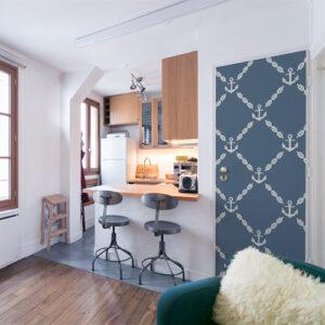 Petit studio bien agencé avec une porte d'entré décoré par un sticker autocollant firse ancres blanches sur fond bleu