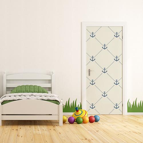 Petite chambre d'enfants avec un sticker adhésif ancres bleues collé sur la porte