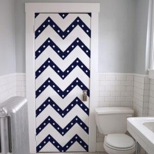 Salle des toilettes dont la porte d'entrée est ornée d'un sticker autocollant chevrons bleus à pois blancs