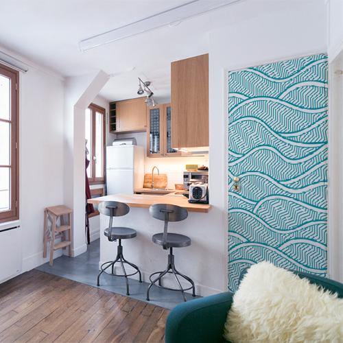 Petit appartement bien rangé avec un sticker bleu représentant des vagues collé sur la porte