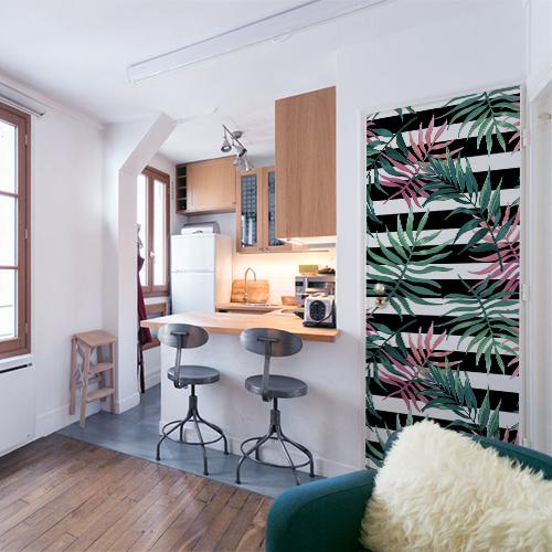 Petit studio dont la porte d'entrée est décorée avec un sticker autocollant fougères vertes et roses
