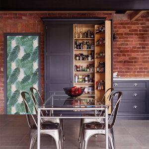 cuisine avec sticker décoratif fougères vertes collé sur la porte d'une cuisine style ancienne usine avec du mobilier en bois et métal et un mur de brique orange