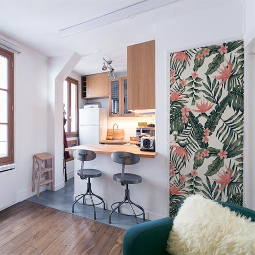 cuisine d'un appartement moderne sous les toits avec sticker motif fleurs exotiques roses collé sur la porte ce qui vient compléter le style tendance et le côté cosy de cet intérieur
