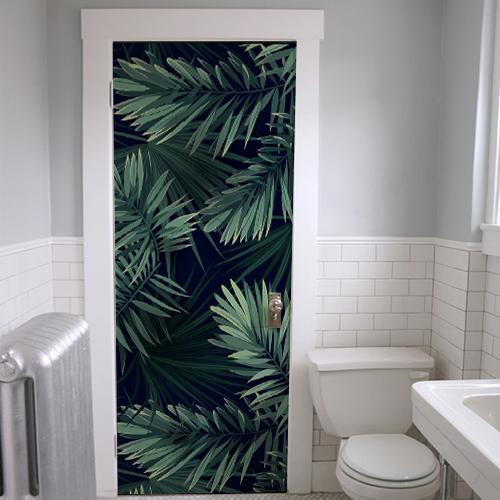Salle de bain transformée avec un adhésif fougère sur fond noir motif fougères vertes sur fond noir collé sur la porte
