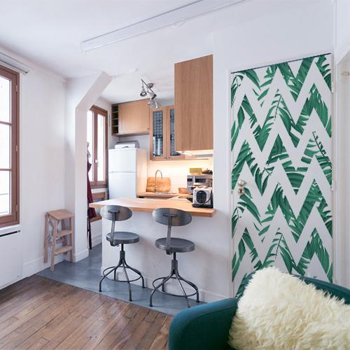 Studio avec cuisine indus et porte personnalisée avec décor adhésif pour porte Jungle chevrons blanc et vert. Cet adhésif collable s'intègre dans un décor moderne usine cosy
