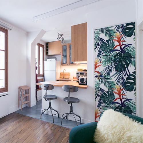 Entrée d'un appartement avec cuisine industrielle et porte personnalisée avec adhésif façon papier peint jungle.